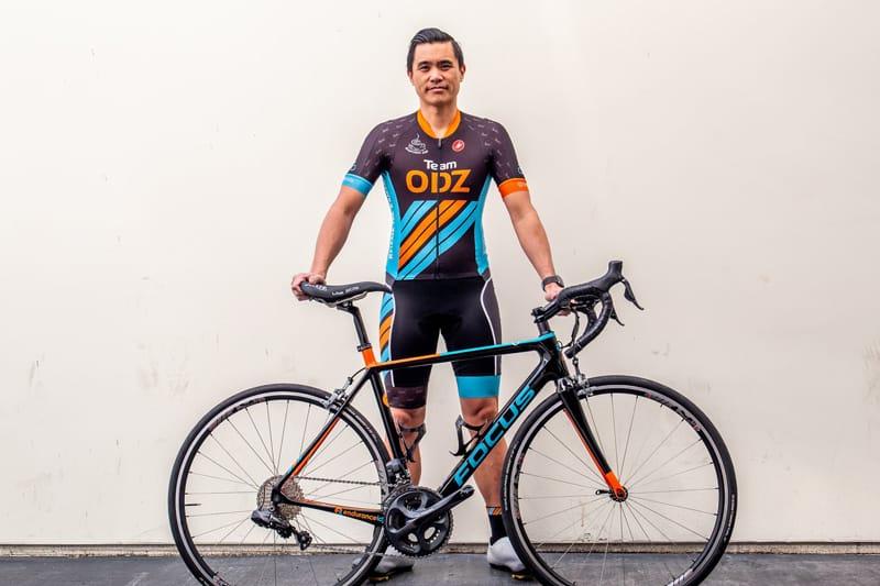 Cyclist Jason Flores holding bike and wearing ODZ kit